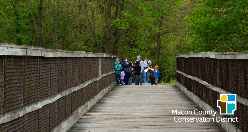 Group of people standing on wooden bridge on the bike trail