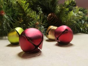 close up of red and green sleigh bells with pine tree branches in background