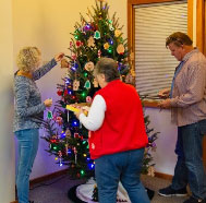 3 volunteers decorating a Christmas tree